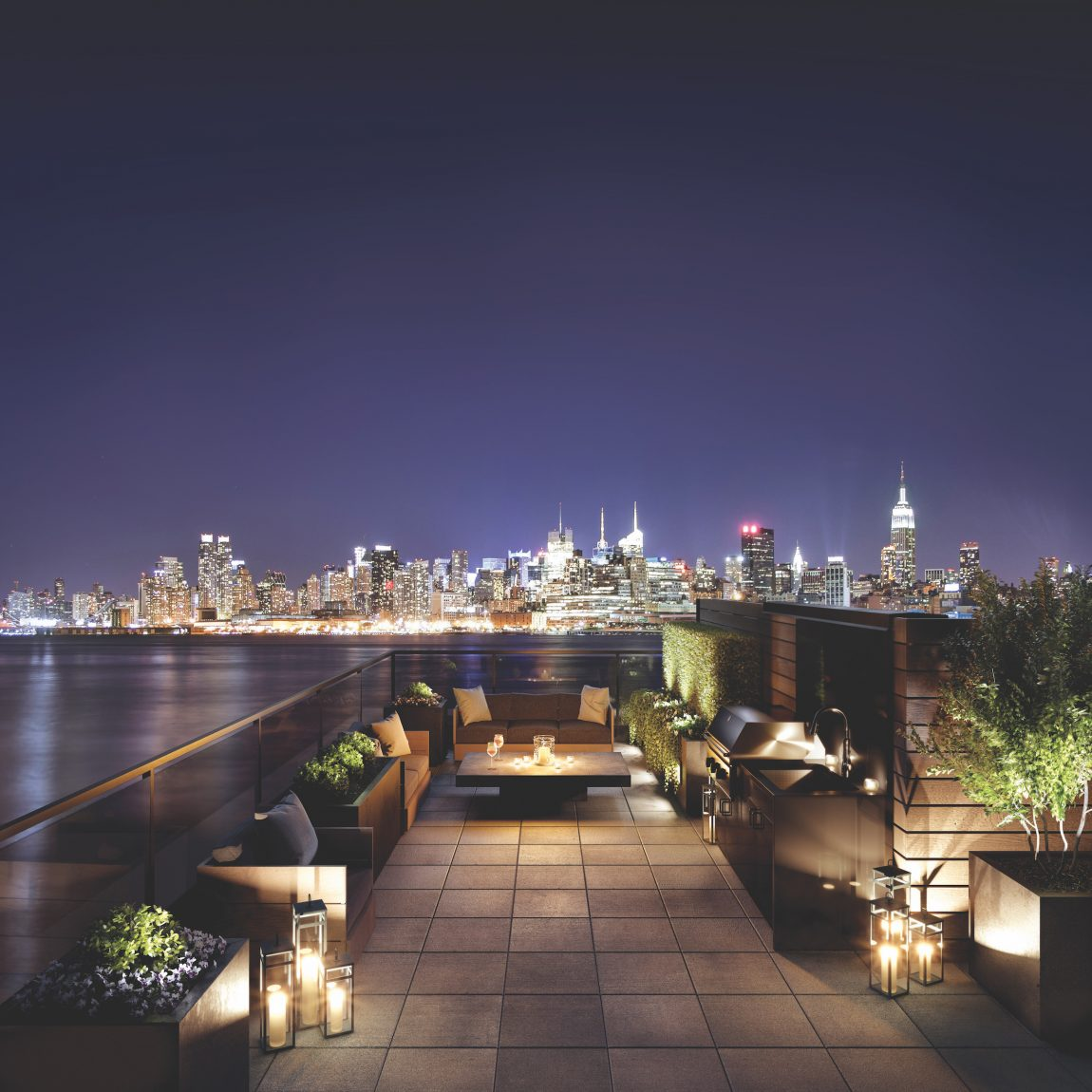 A patio with a fire pit overlooking New York City at night from across the river.