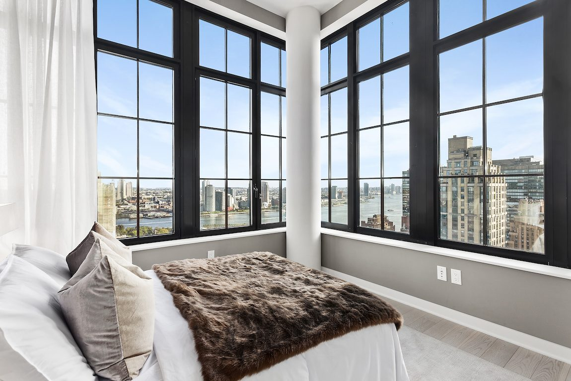 Bedroom with black trimmed windows overlooking New York City