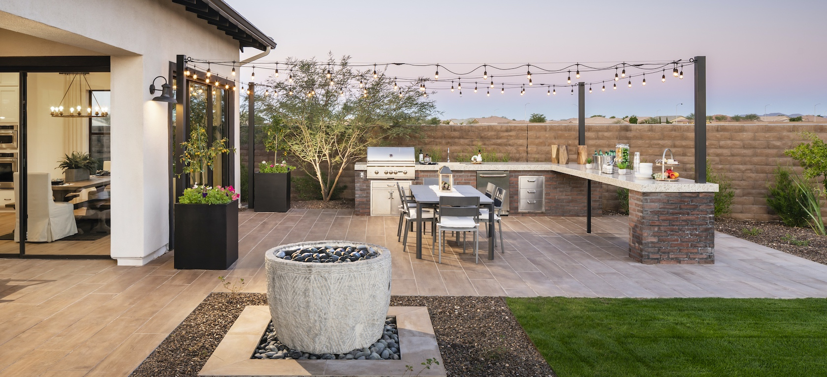 Outdoor kitchen with string lights in the backyard of a luxury house in Arizona.