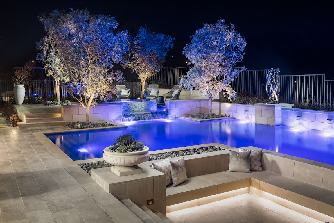 Beautiful landscaping featuring an outdoor pool with sitting area.