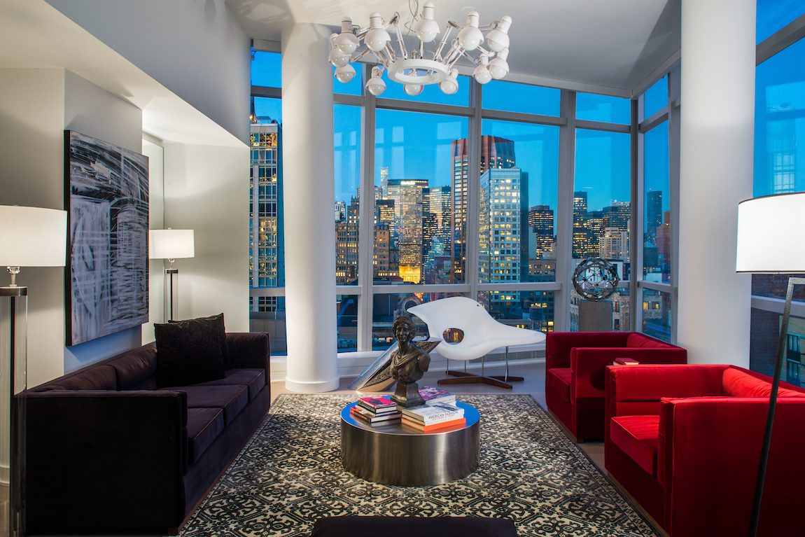 Living room with red velvet chairs and black sofa with view of New York City