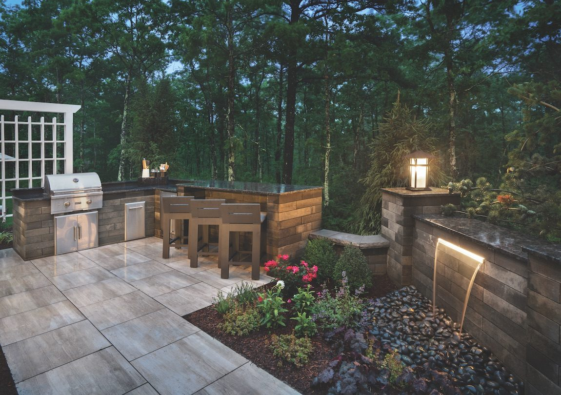 Outdoor kitchen with waterfall and landscaping.