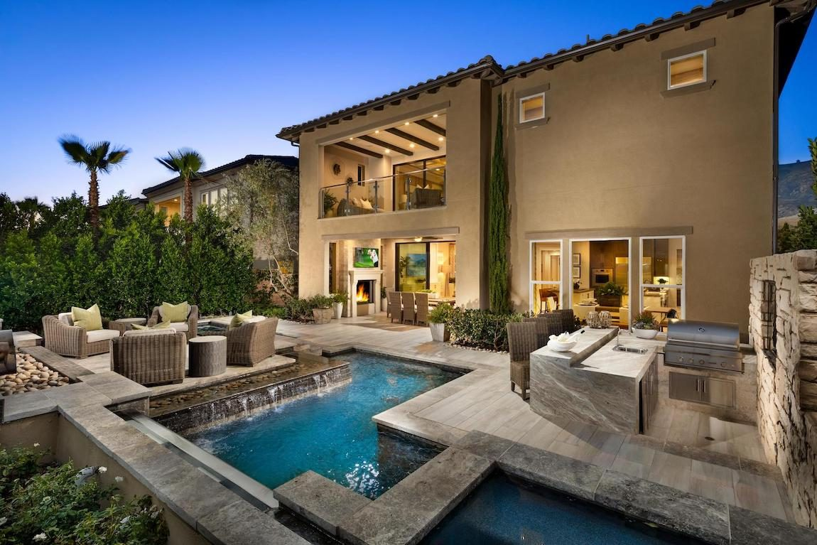 Outdoor kitchen, pool and wet bar in backyard oasis.