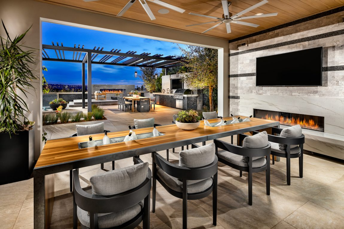 Happy hour spot with fireplace and pathway to backyard kitchen.