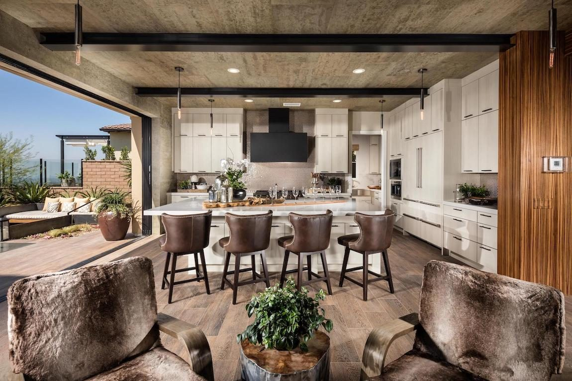 Indoor to outdoor kitchen with barstool chairs.