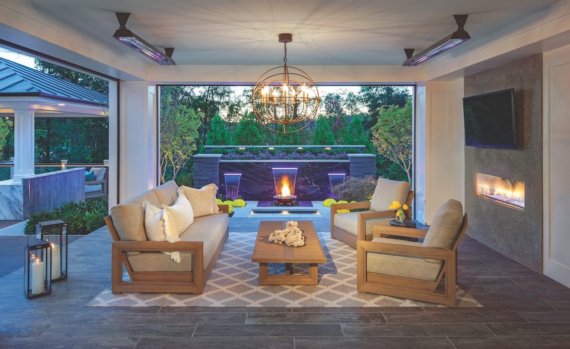 Outdoor living with area rug, lighting, fireplace and waterfall.
