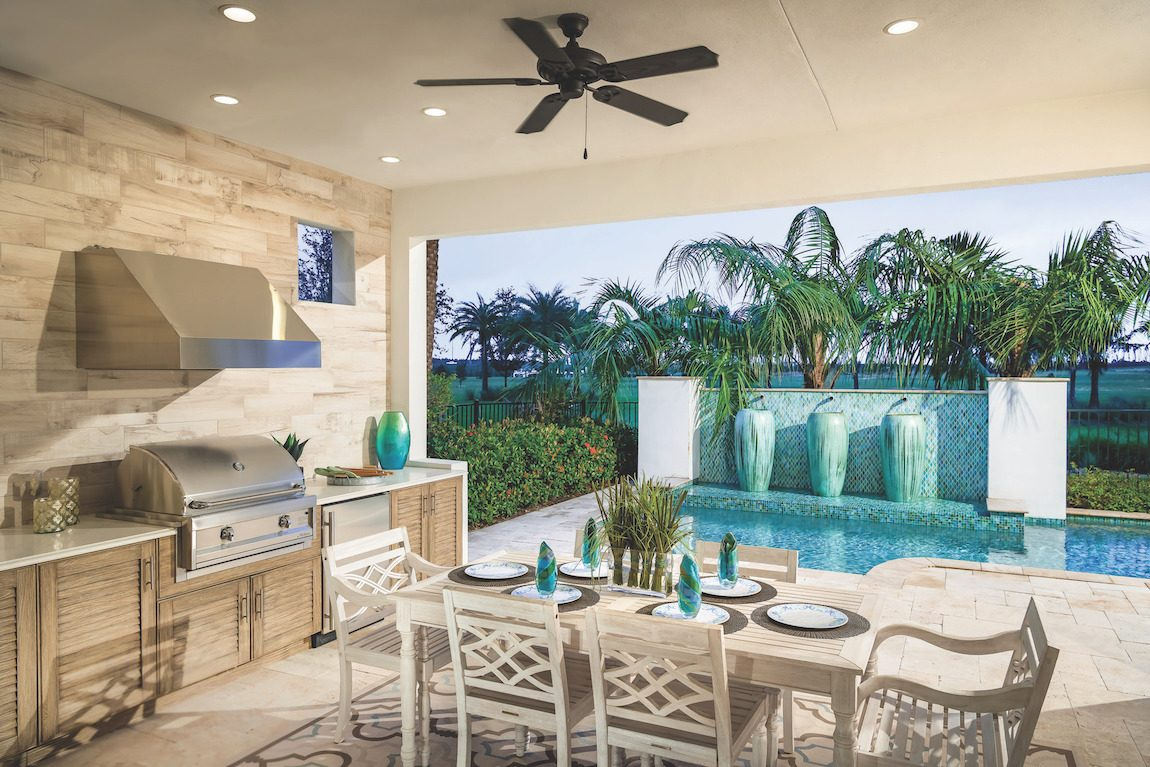 Outdoor kitchen with pool and dining table.
