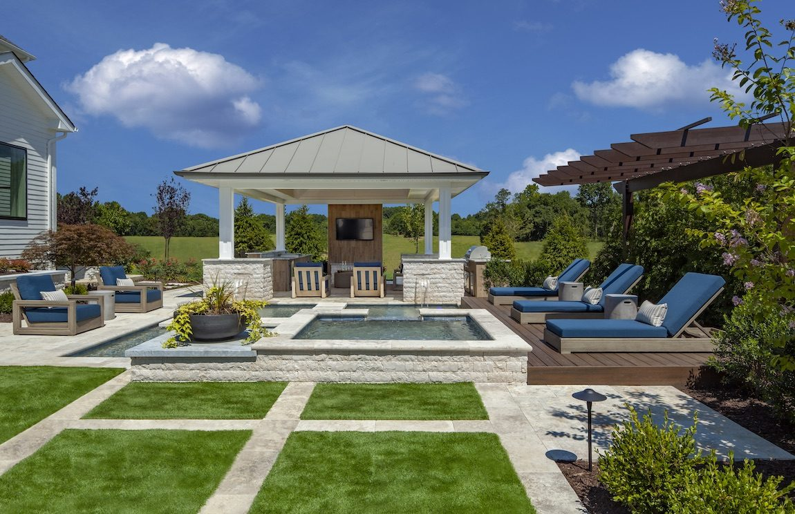 Patterned lawn with outdoor bar, pool and lounge chairs.