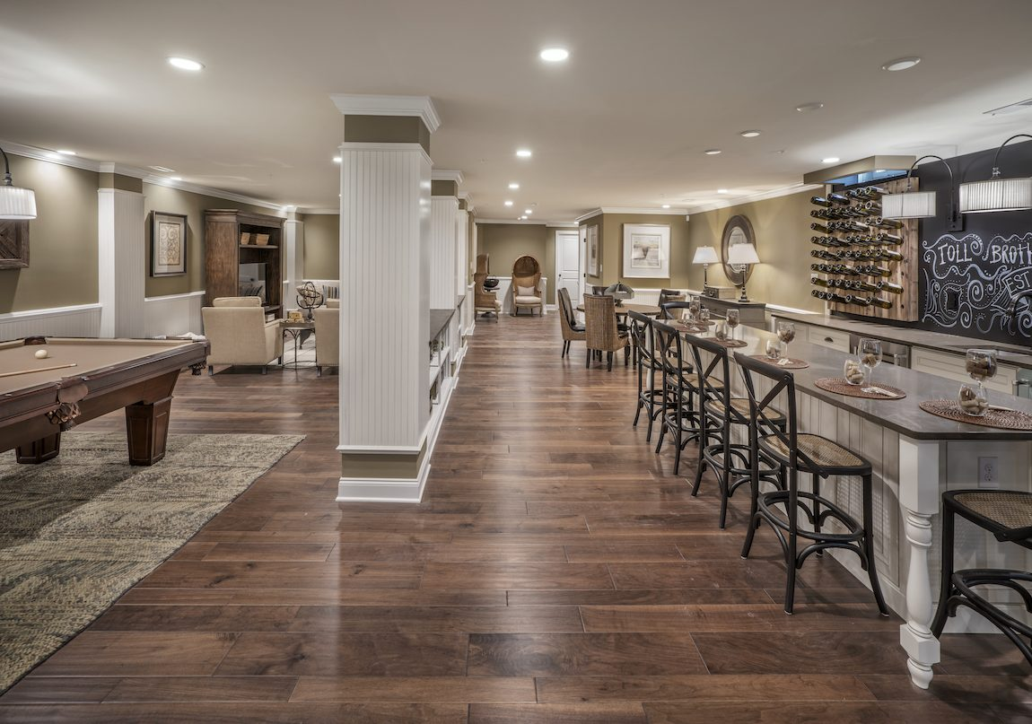 Large basement area with seating area, hardwood floors, and wet bar.
