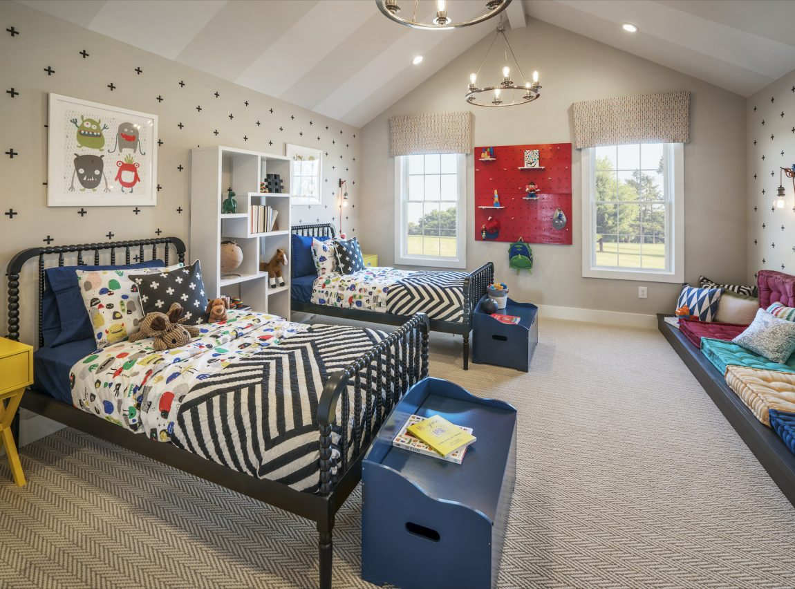 Spacious kids bedroom featuring two eye-catching beds and large chests for storage.