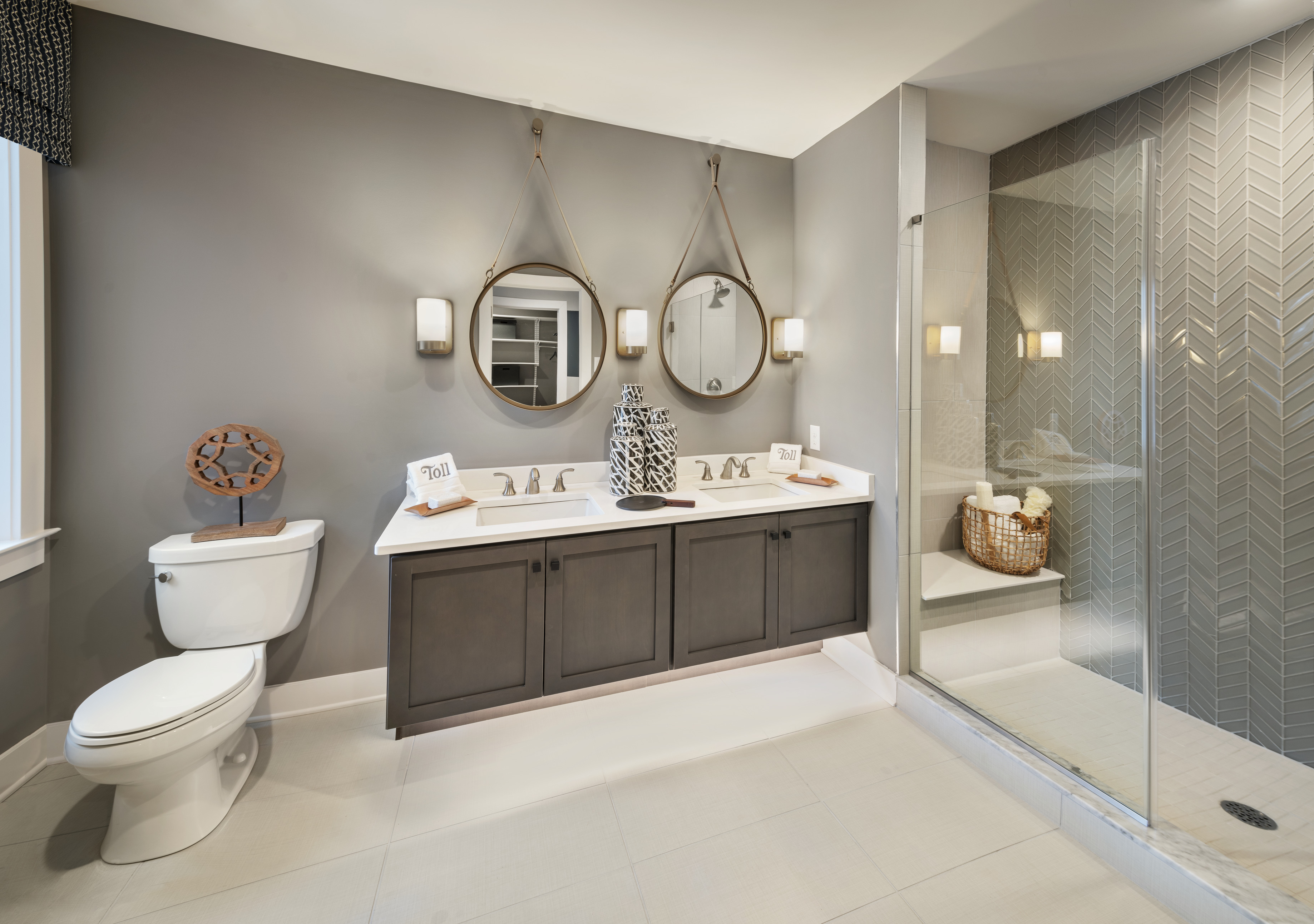 Bathroom with Repose Gray painted walls, dual vanity, toilet, and walk-in shower.