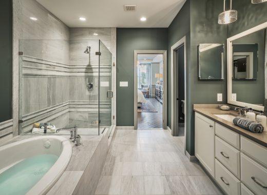 Bathroom with striking green wallls, walk-in shower, bathtub, vanity, and marble flooring