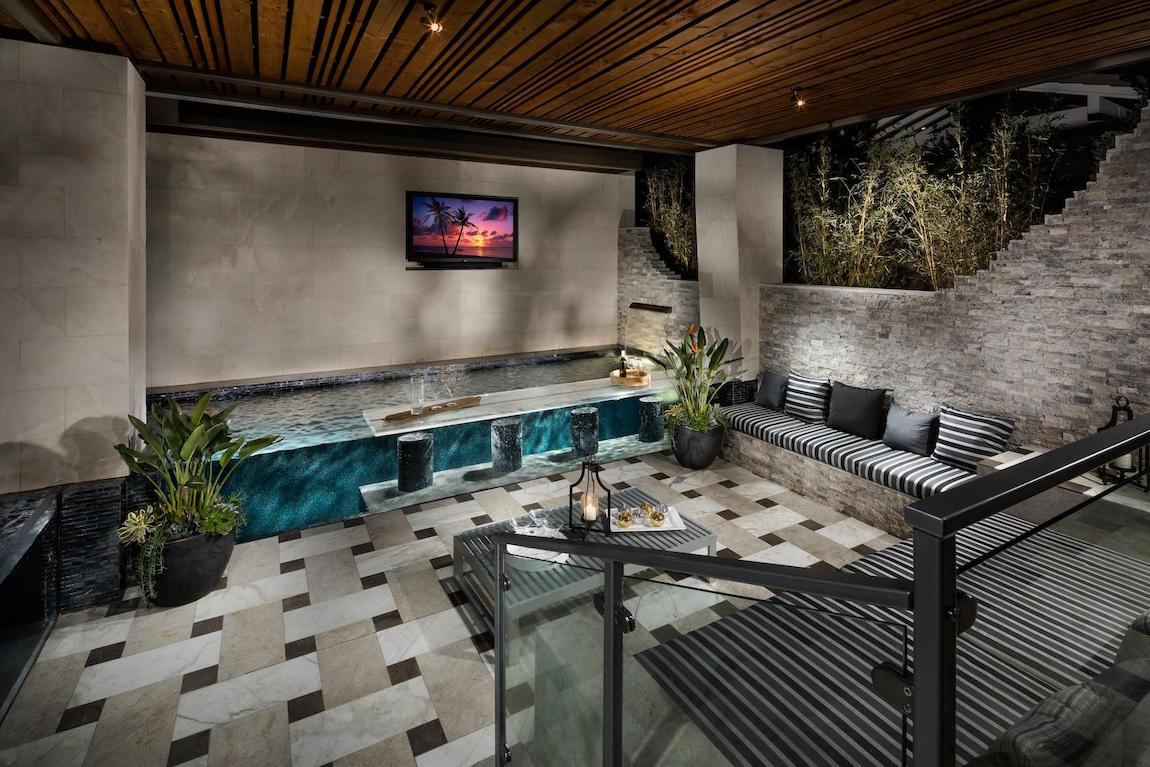 Indoor to outdoor pool bar with wall couch sitting area.