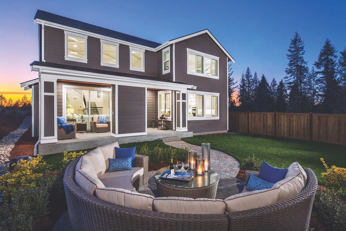 Backyard with circular fire pit and furniture.