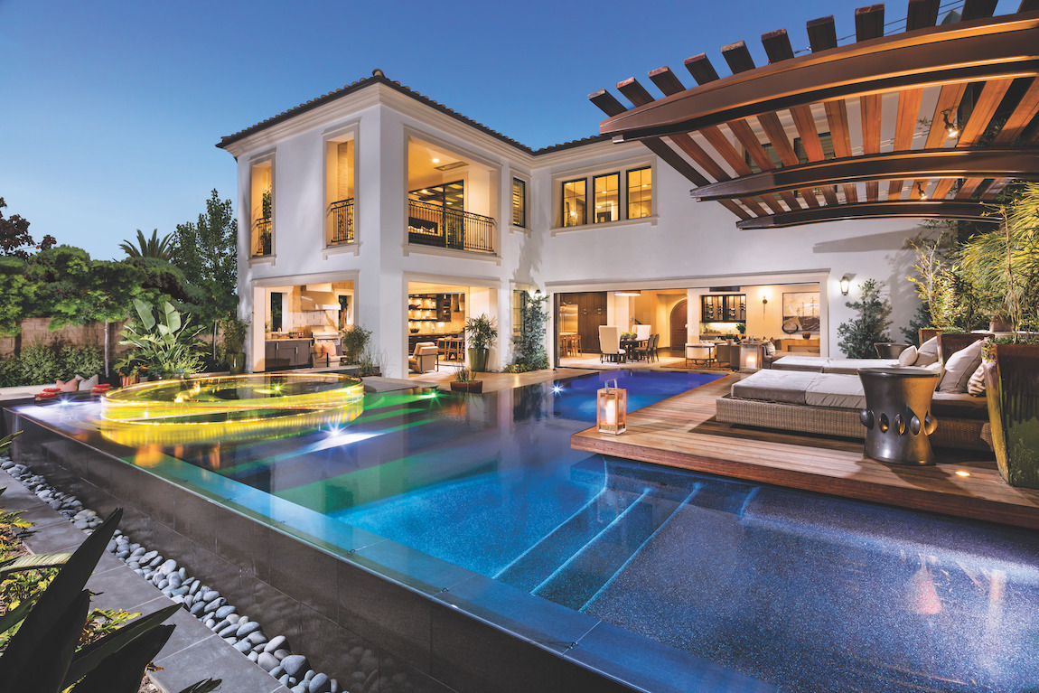 Large pool with lounge beds, lighting, and stone work.