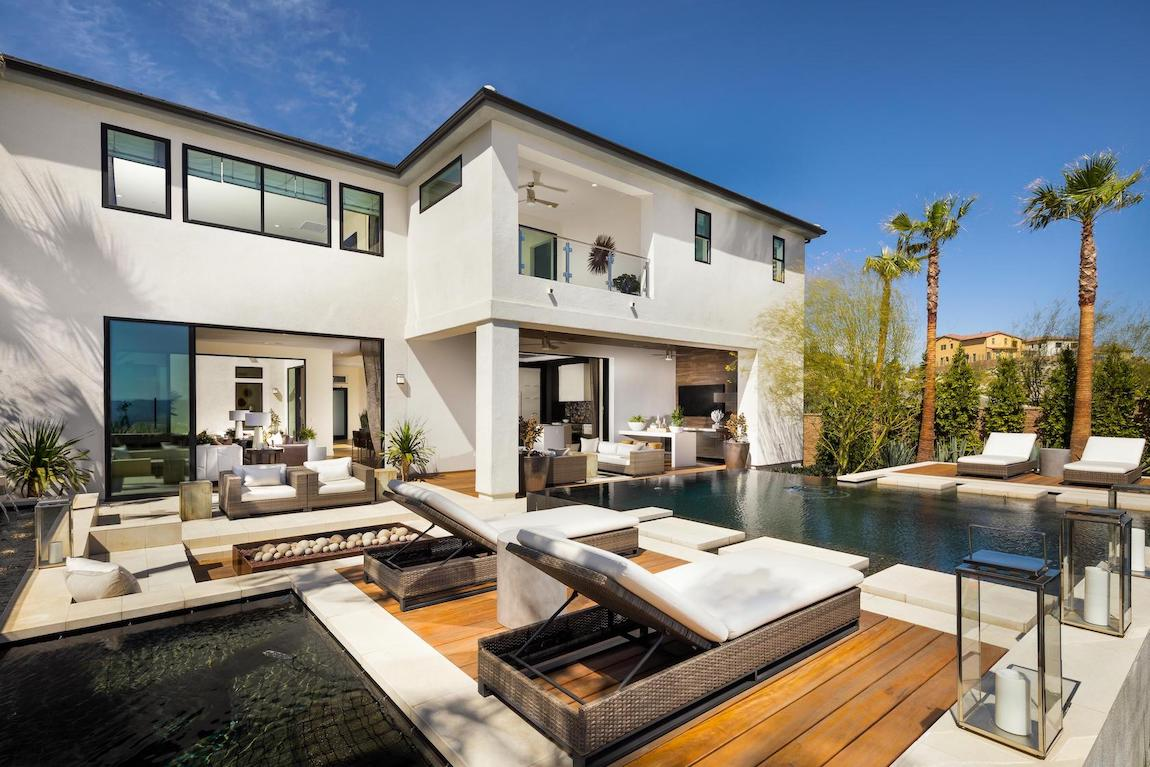White exterior of home with pool, lounge chairs, and palm trees.