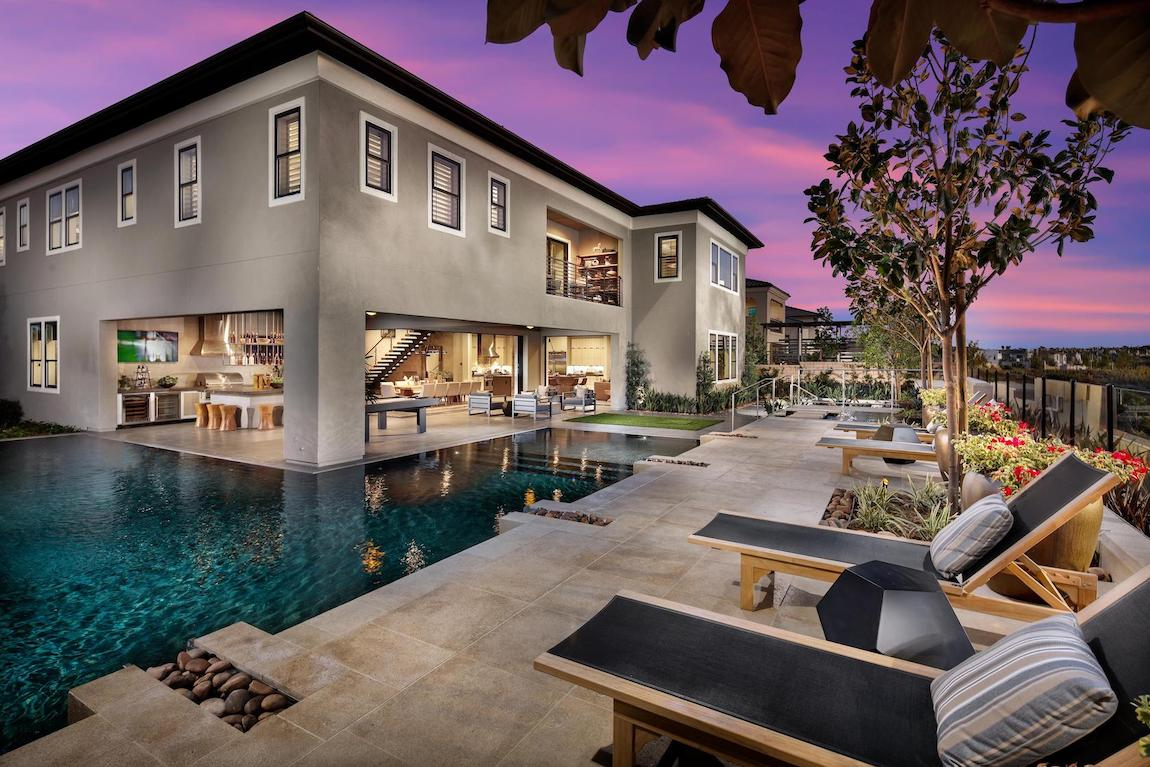Black lounge chairs with pillows next to a luxury pool with stone work and entry from house.
