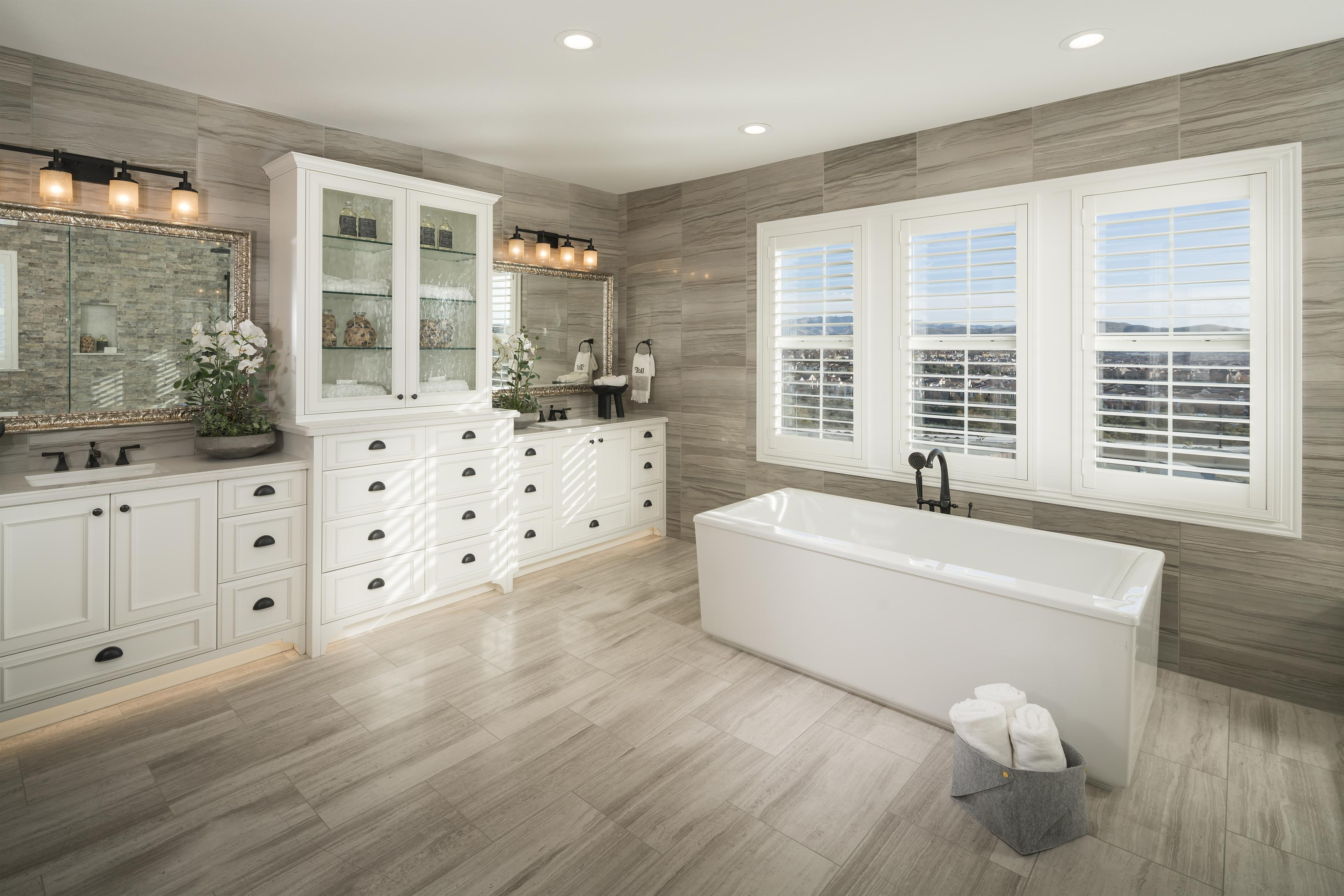 Bathroom with impressive freestanding bathtub, dual vanities, and white cabinetry.