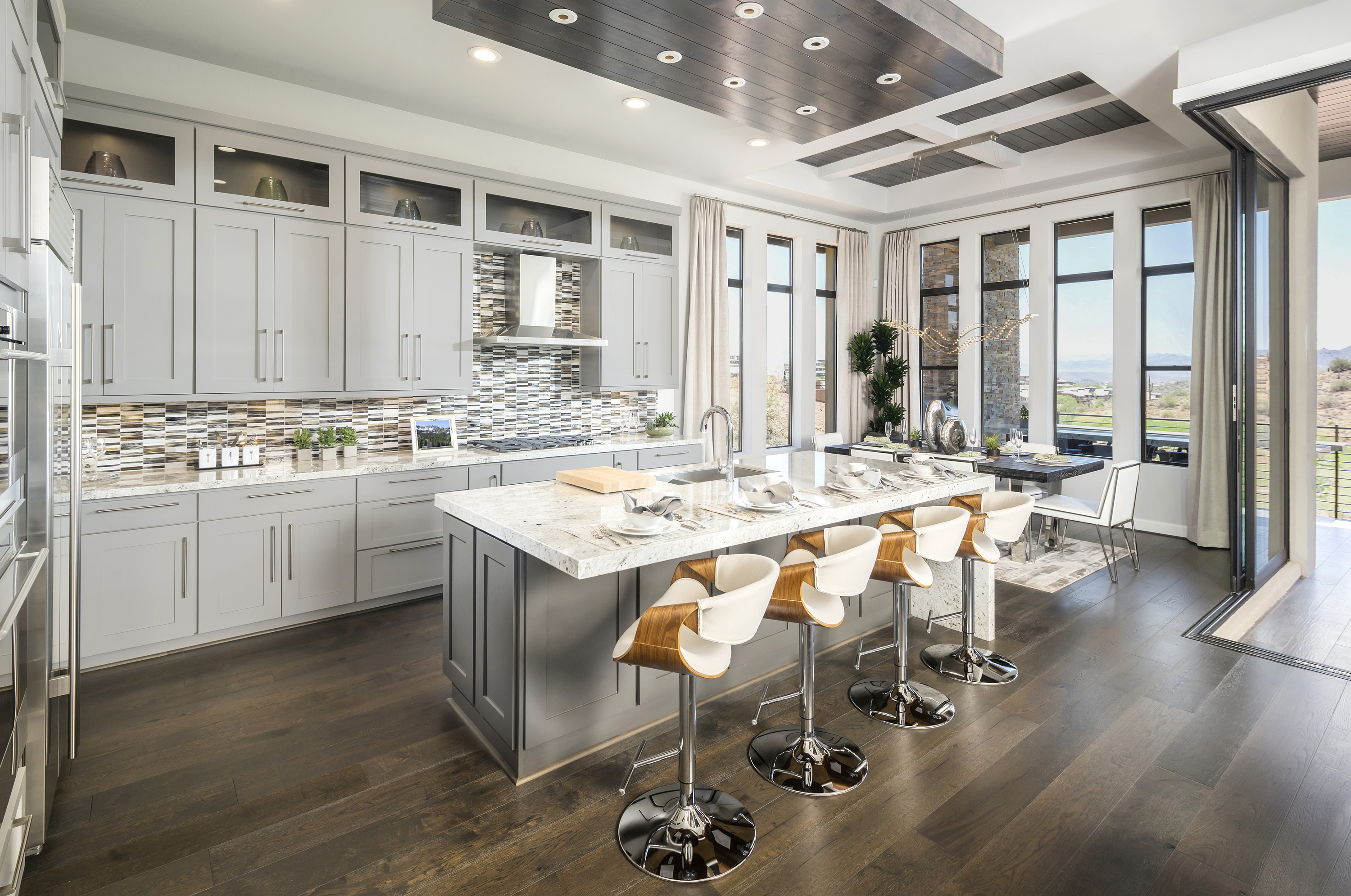 Beautiful kitchen with island seating, side dining area, and metallic accents