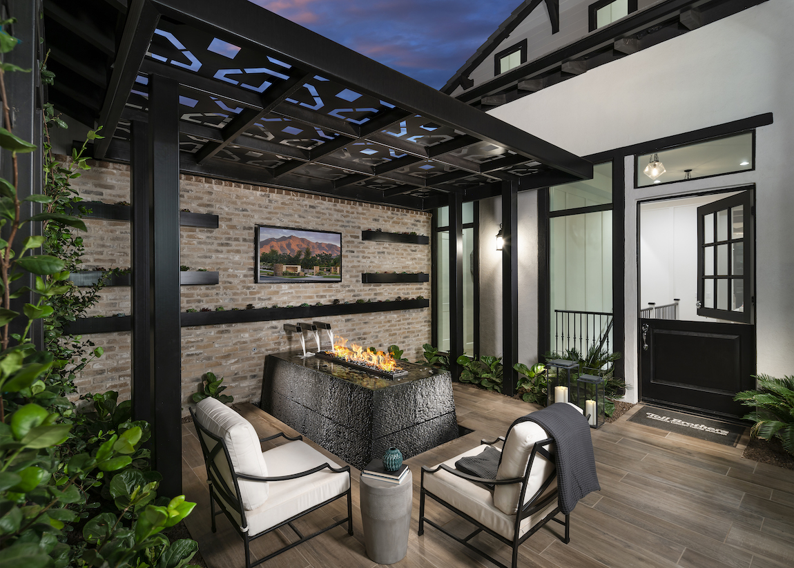 Backyard with fire pit and waterfall with white patio chairs, television and metal detailed awning.
