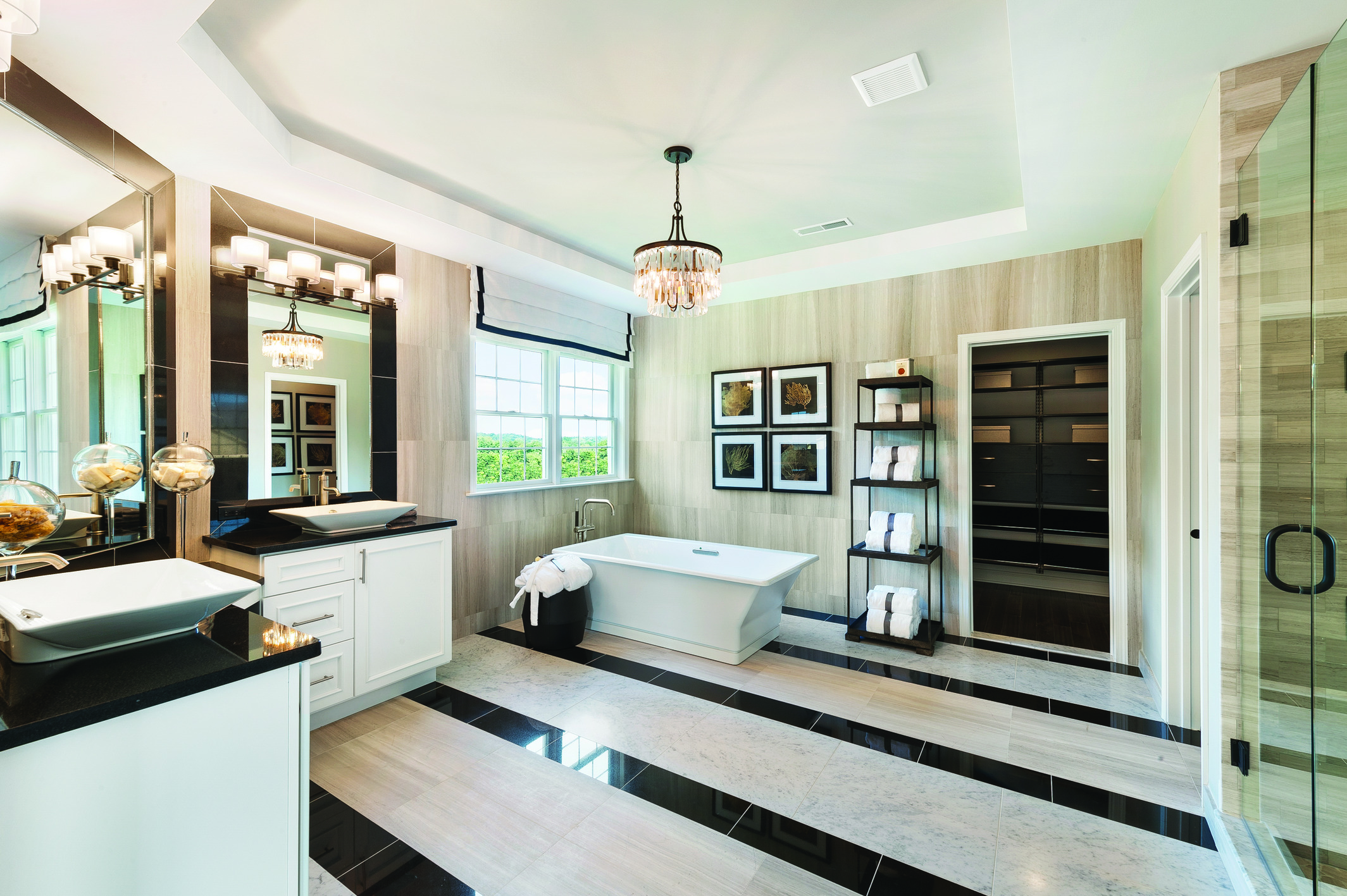 Bathroom with raised ceiling, lavish chandelier, freestanding bathtub, and dual display vanity
