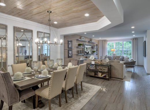 Dining room area with chandelier lighting, which leads into a family room