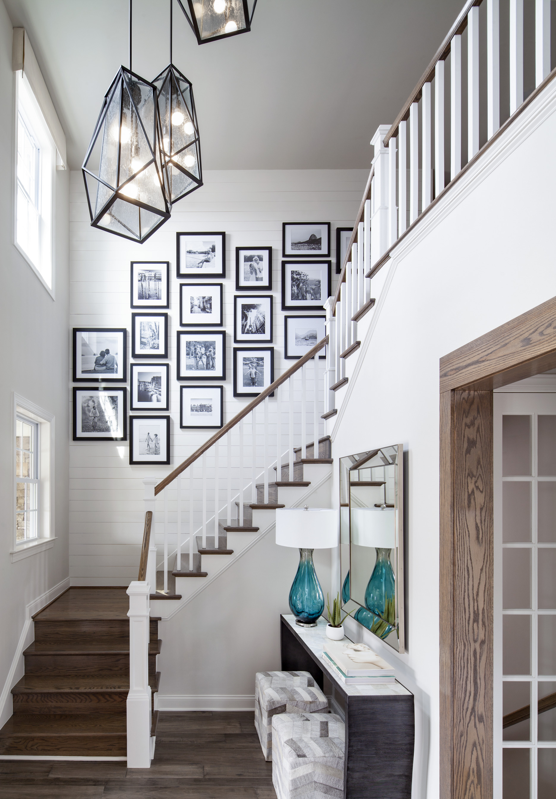 Foyer area staircase with striking pendant lighting fixtures and a collage of picture frames on the wall