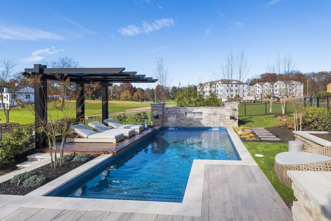 Outdoor pool with seating area and landscaping.