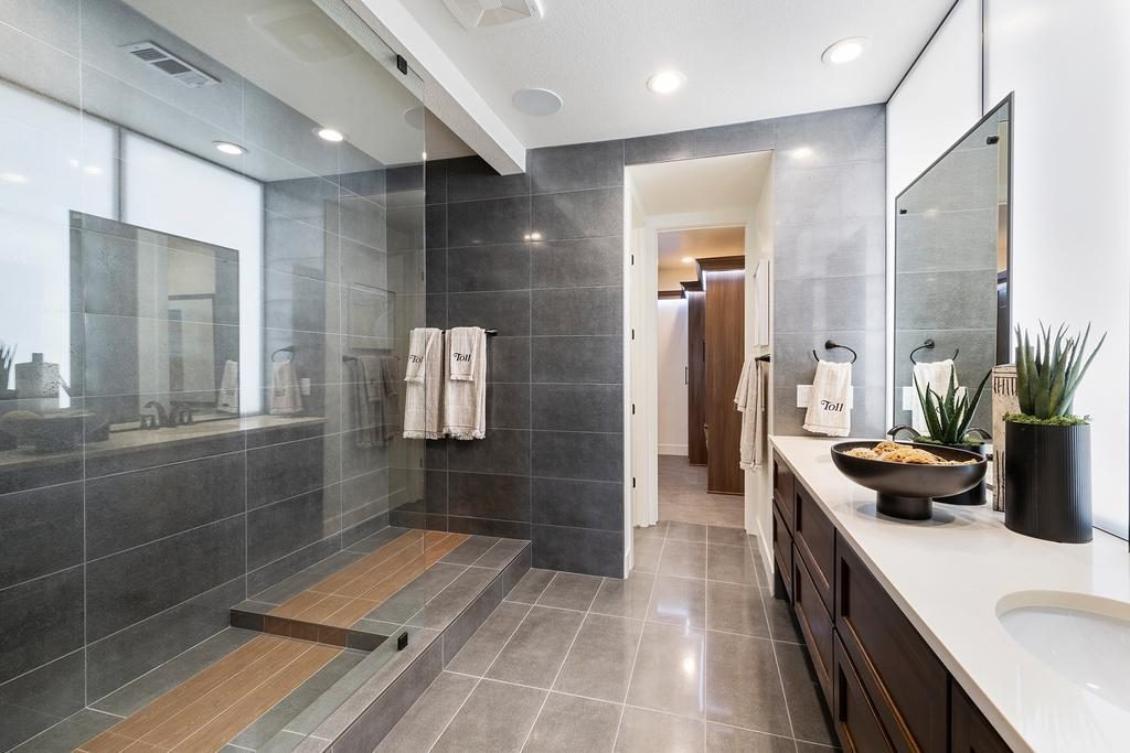 Bathroom with gray floor and wall tiling, walk-in shower, and dual vanity display