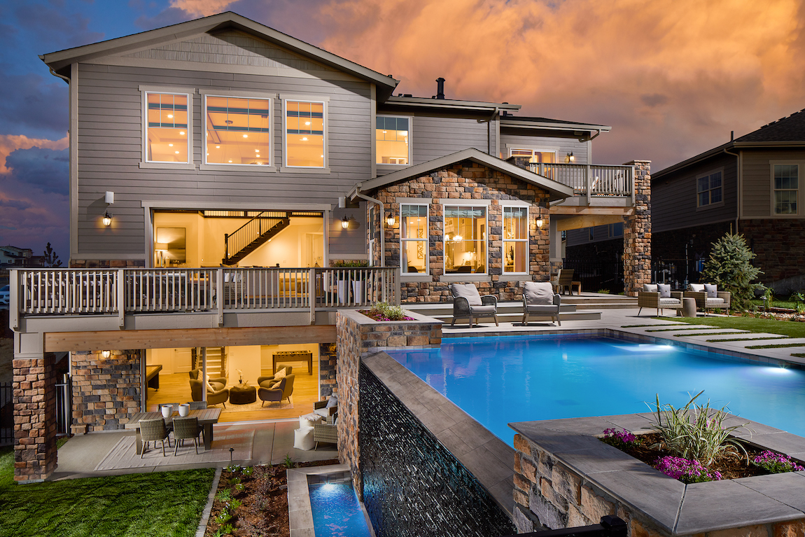 Backyard exterior of luxury home with pool, water fountain, deck, stone facade and sitting area.