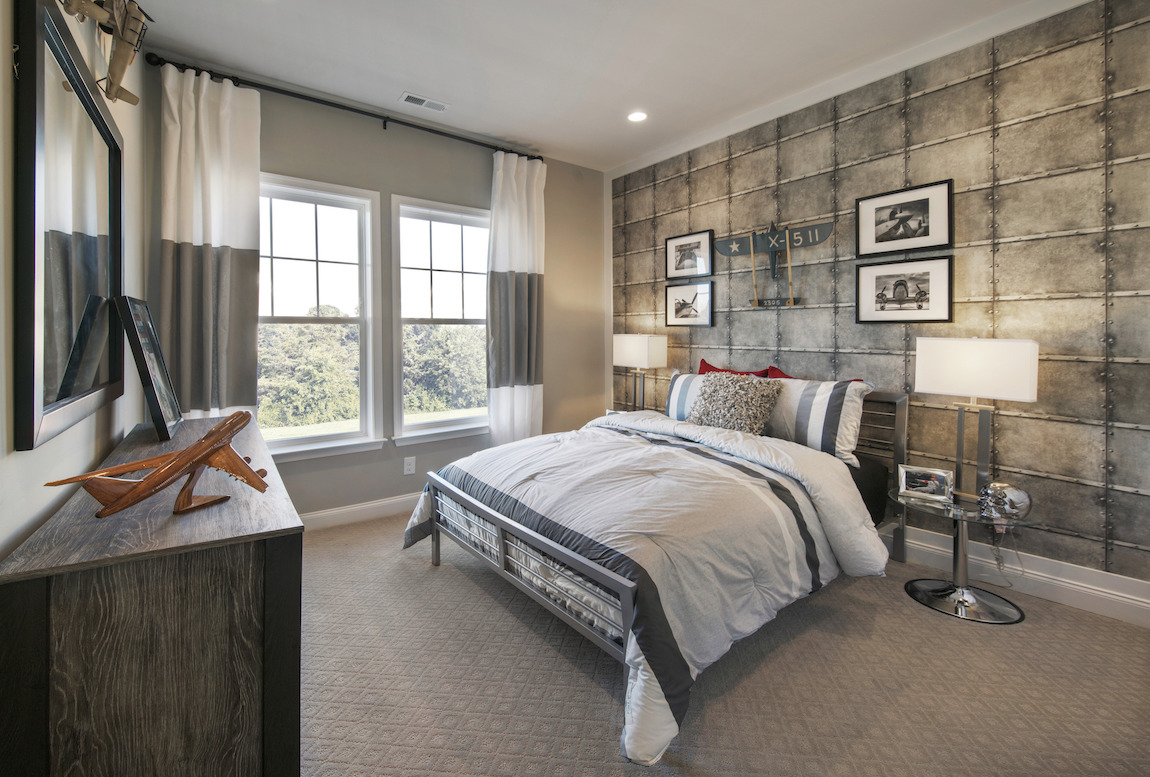 Teen bedroom highlighted by pictures, decorative pieces, and wall paneling geared towards aviation theme
