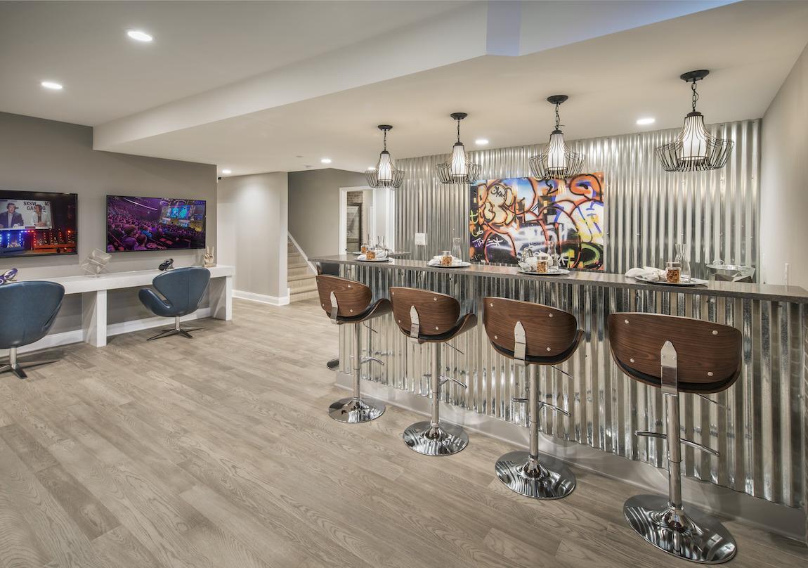 Basement bar boasting metallic design, graphic wall art, and barstool seating
