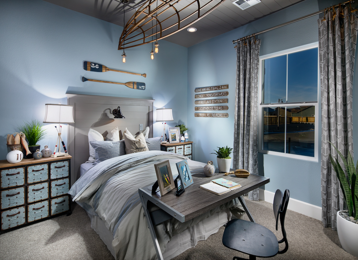 Light blue teen bedroom featuring fishing theme and workplace at foot of the bed