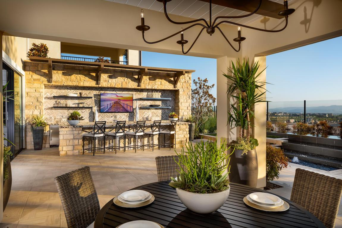 Outdoor bar featuring stone siding, ample shelving, TV display, Long Island, and outdoor chair seating.