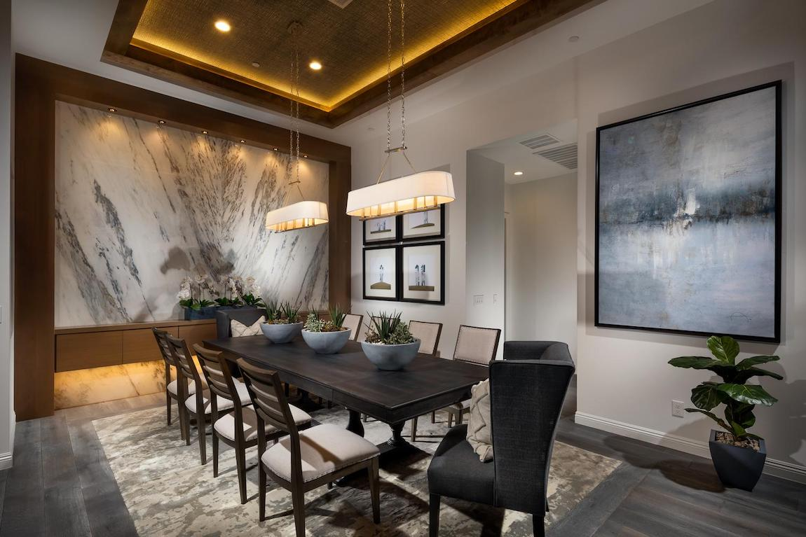 Formal dining area highlighted by tray ceiling with accent lighting.