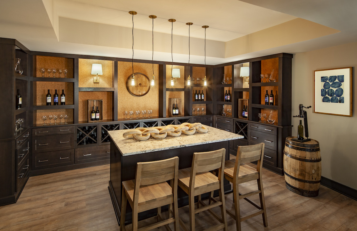 Home bar featuring classy, dark toned theme with charming pendant lighting and cabinetry.