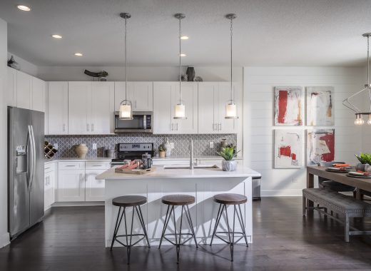 White kitchen with island and wooden bar stools.