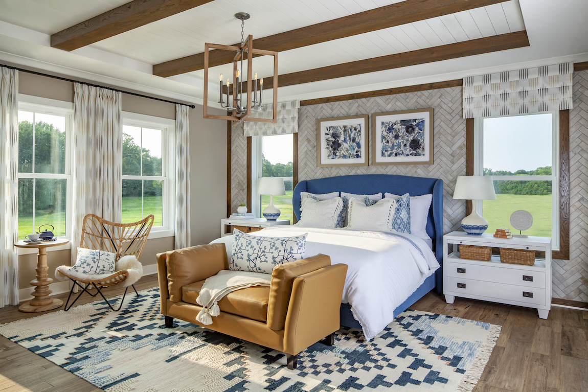 Modern farmhouse bedroom featuring area rug, patterned windows curtains, beam ceiling and matching night stands