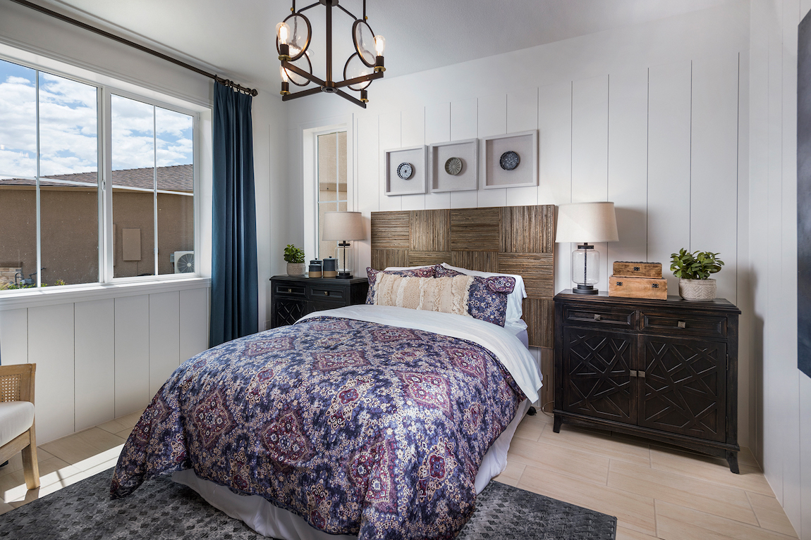 Teen bedroom featuring wooden headboard and three-wide picture frames above