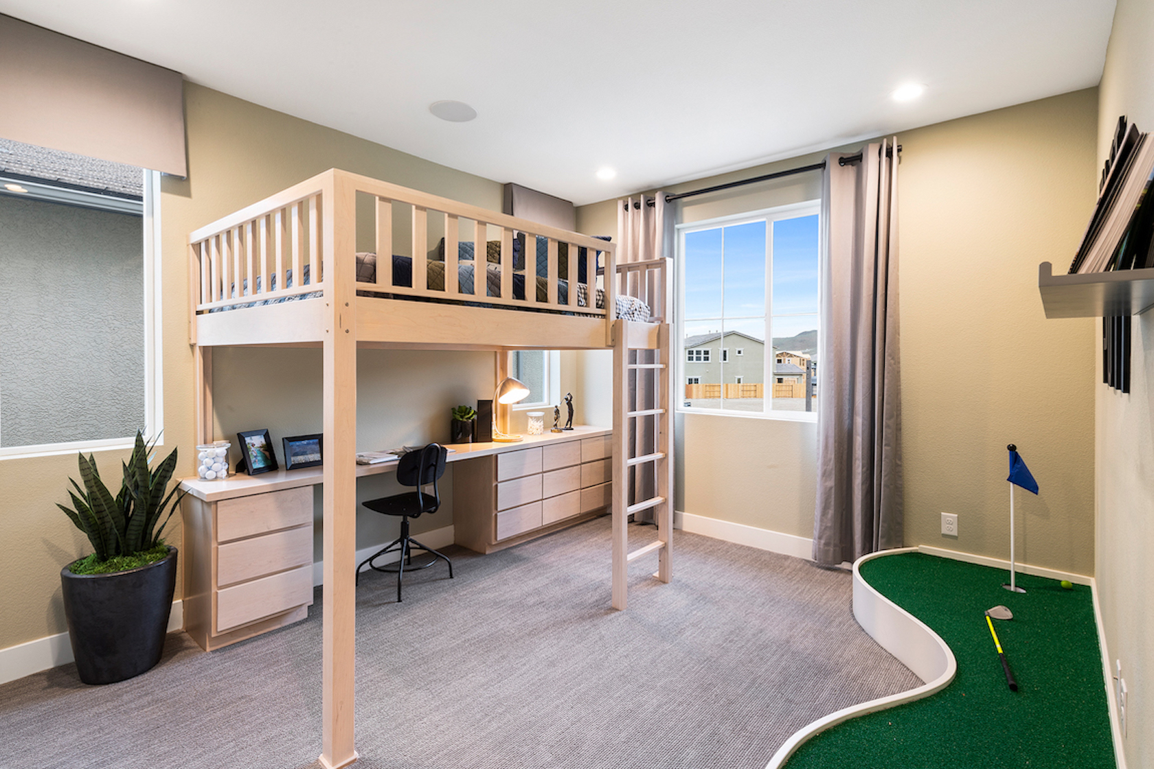 Teen bedroom with loft bed, workspace, and putting green