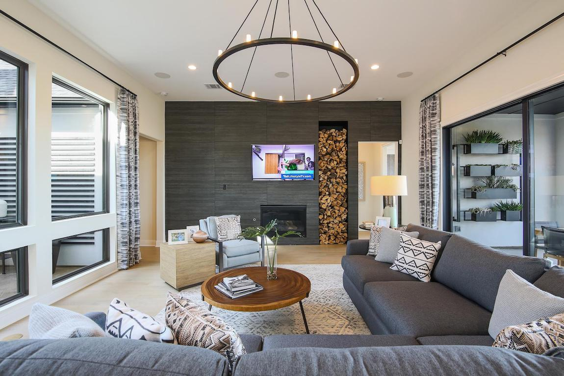 sleek, modern living room featuring dark, textured wall and ring lighting fixture