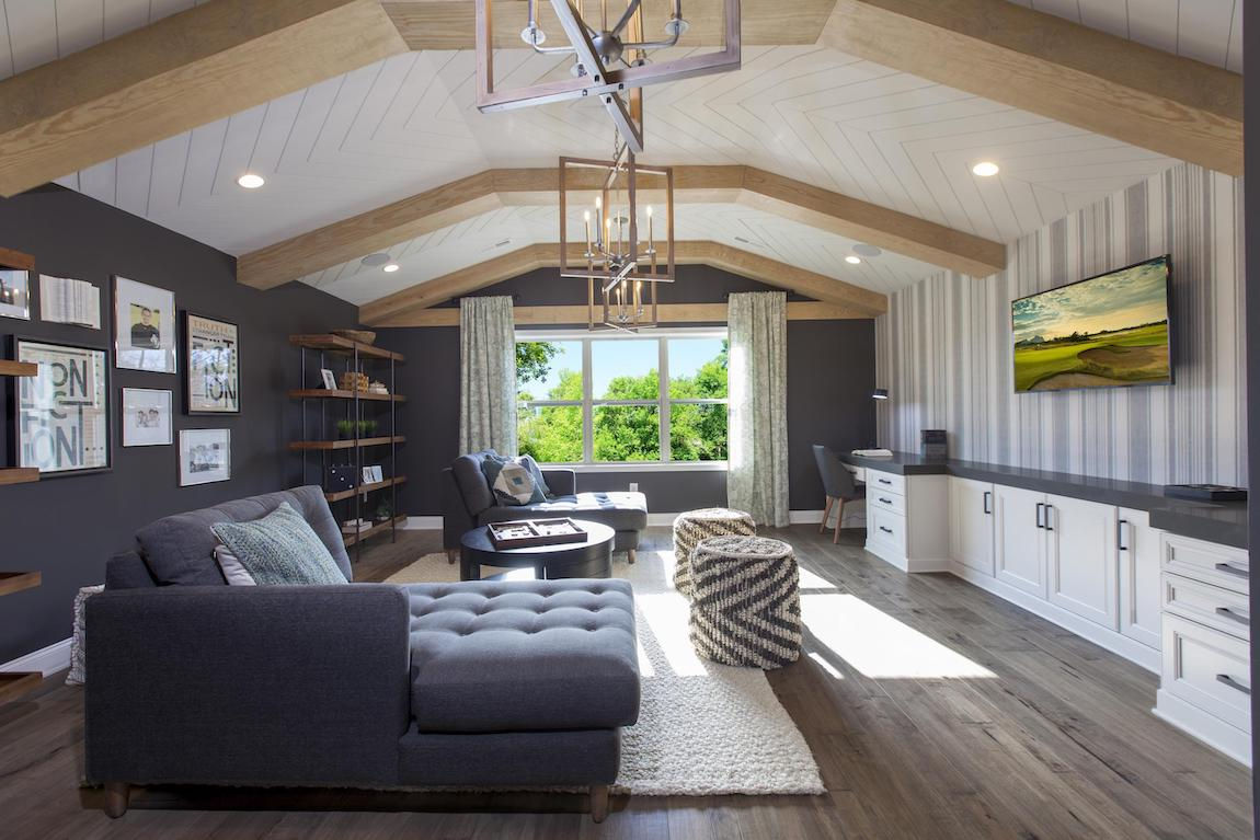 Modern farmhouse den highlighted by wood flooring and raised ceiling with beams