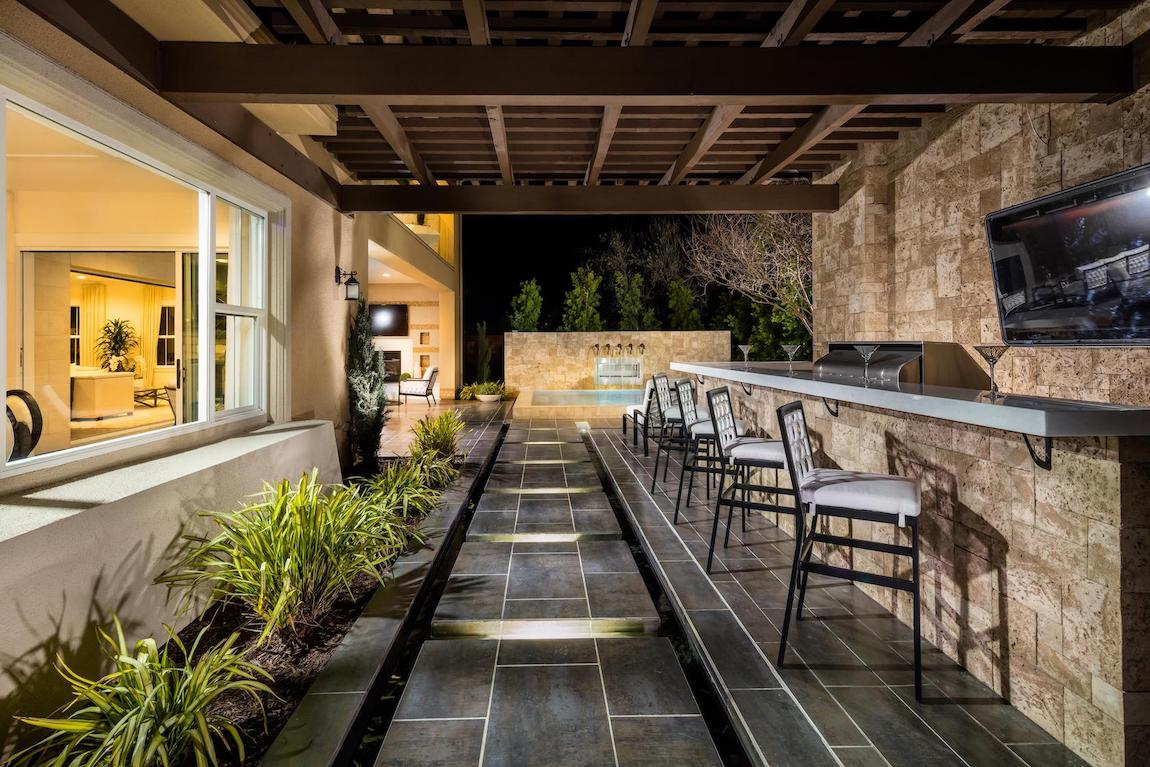Outdoor space highlighted by long backyard bar