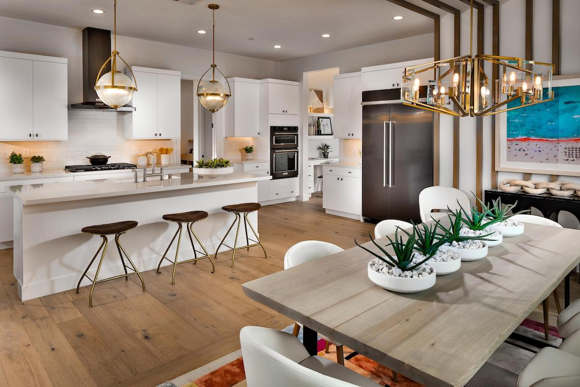 Modern kitchen with white color scheme featuring globe pendant lights and sleek island with faucet
