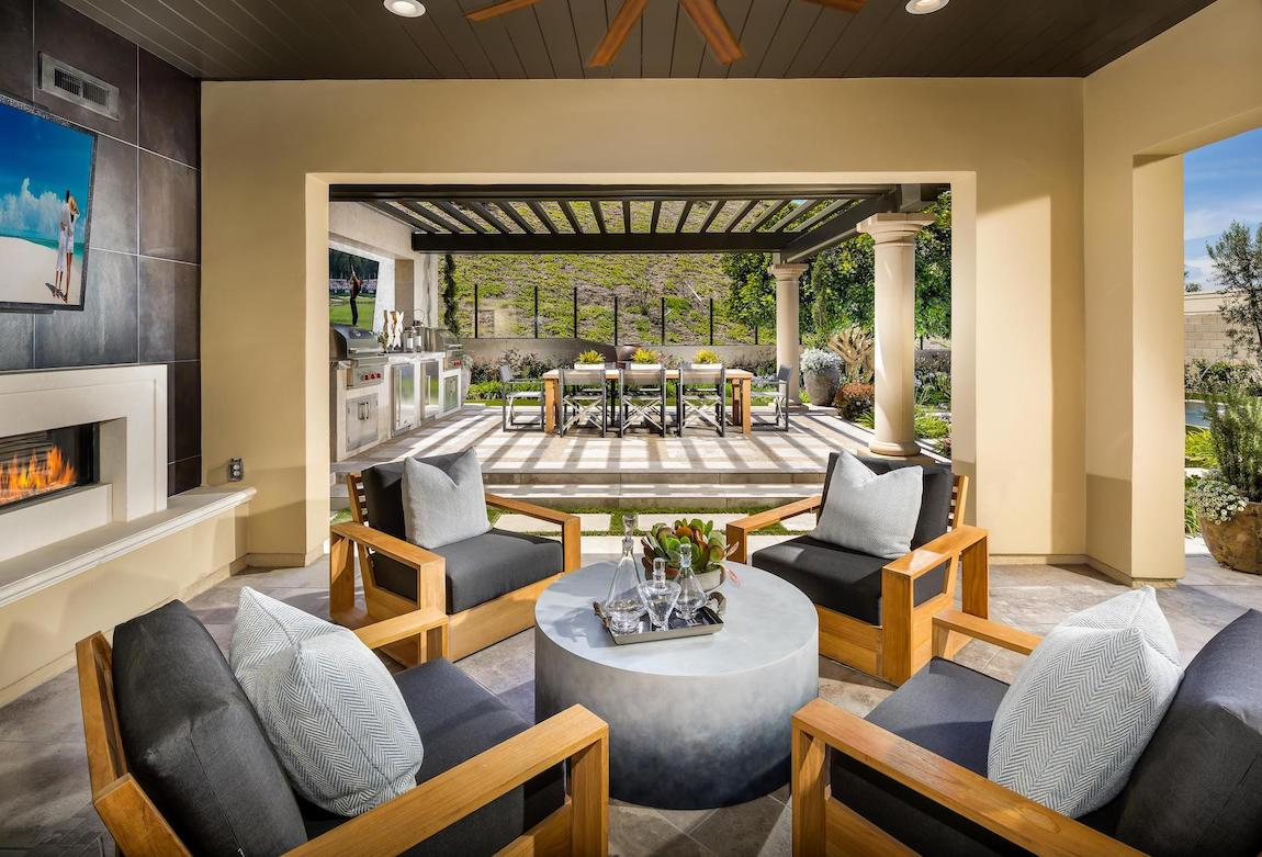 Grand patio design featuring a dining space and covered lunge area with tv and fireplace.