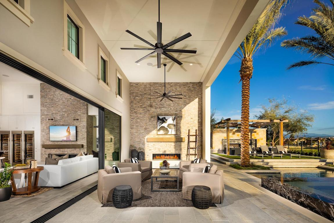 Lovely patio design with tall ceiling, dual fans, and fireplace