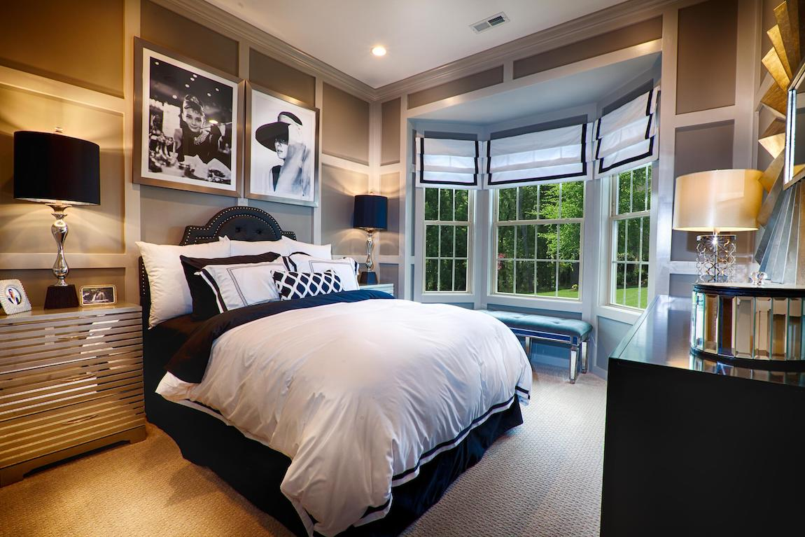 Bedroom with ample natural lighting, soft wall colors, comfy headboard, and centered bed.