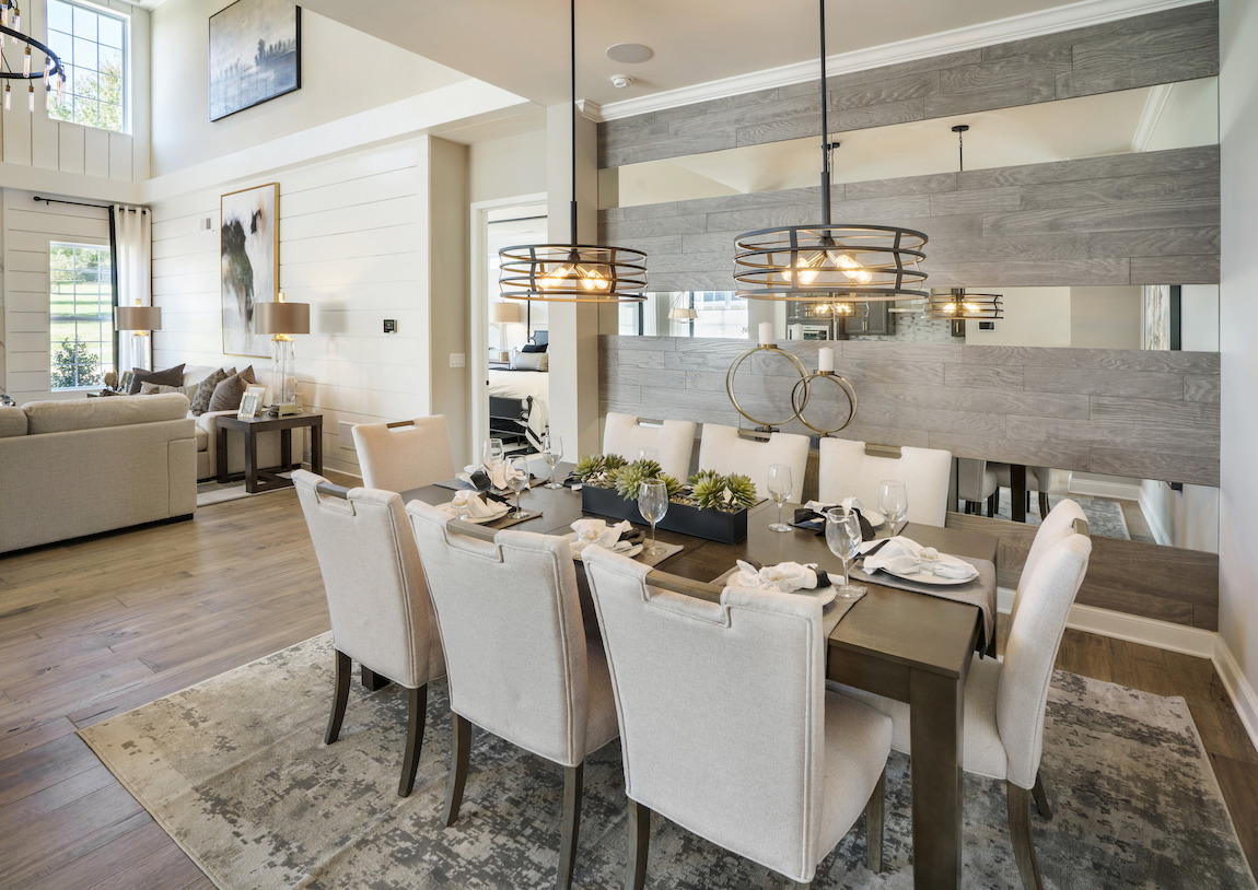 Luxury Dining Room featuring mirrored wood panel, bronze drum light fixtures, and modern Persian rug
