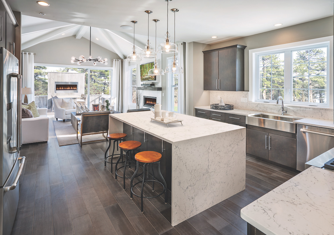 Minimalist Kitchen highlighted by staggered pendants, charcoal slab cabinets, and marble waterfall island.