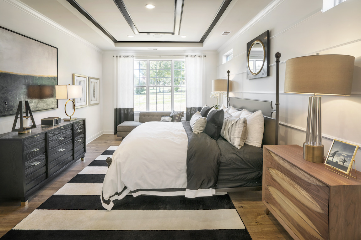 Master bedroom highlighted by contrasting black and white ceiling details and area rug